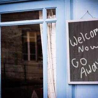 blue door with chalkboard saying Welcome! Now GO AWAY!